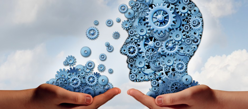 Training and development business education concept with a hand holding a group of gears transfering the wheels of knowledge to a human head made of cogs as a symbol of acquiring the tools for career learning.
